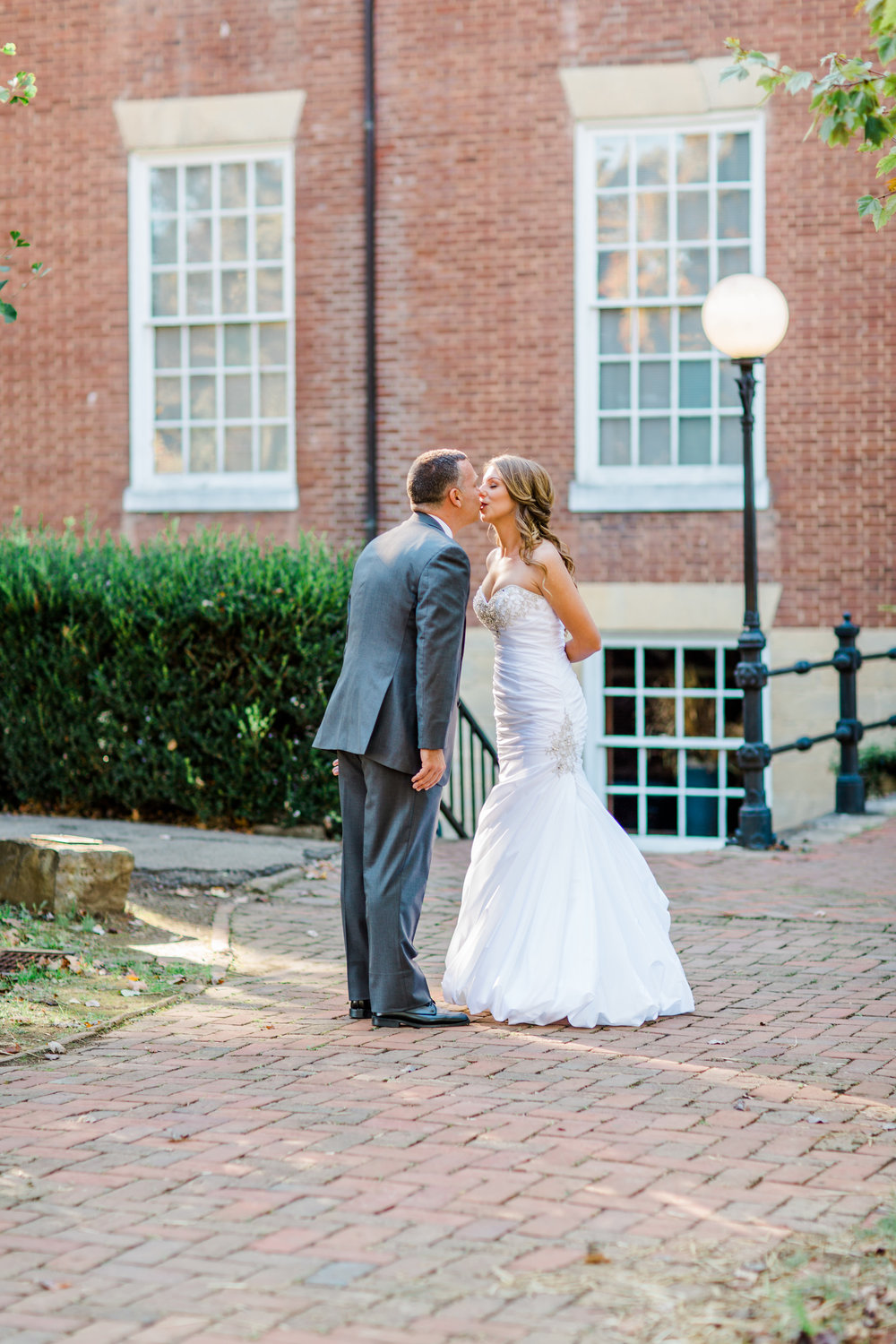 Bride and groom kissing outside Oscar-Getz Museum of Whiskey History during their Bardstown, Ky wedding