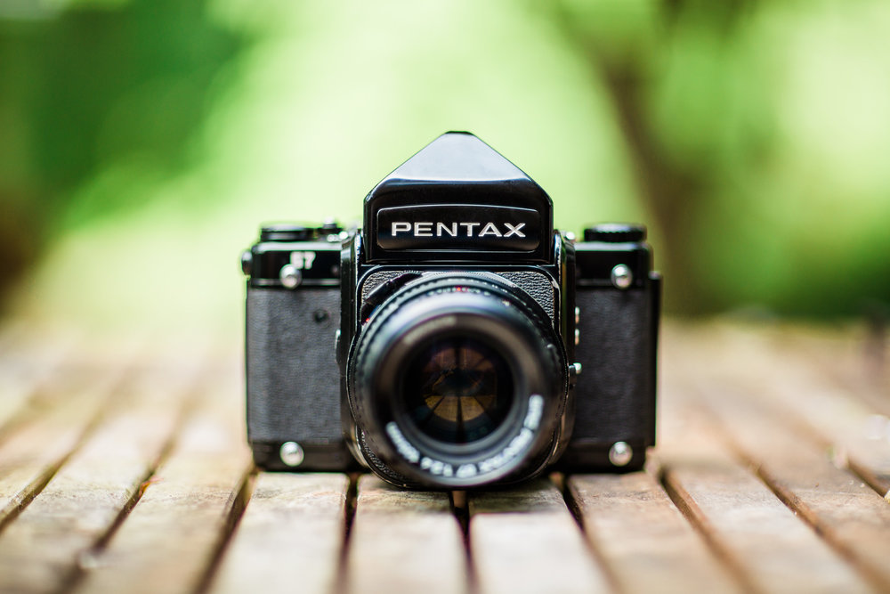 Picture of a Pentax 67 Film Camera with Prism and Pentax 105mm f/2.4 lens sitting on table