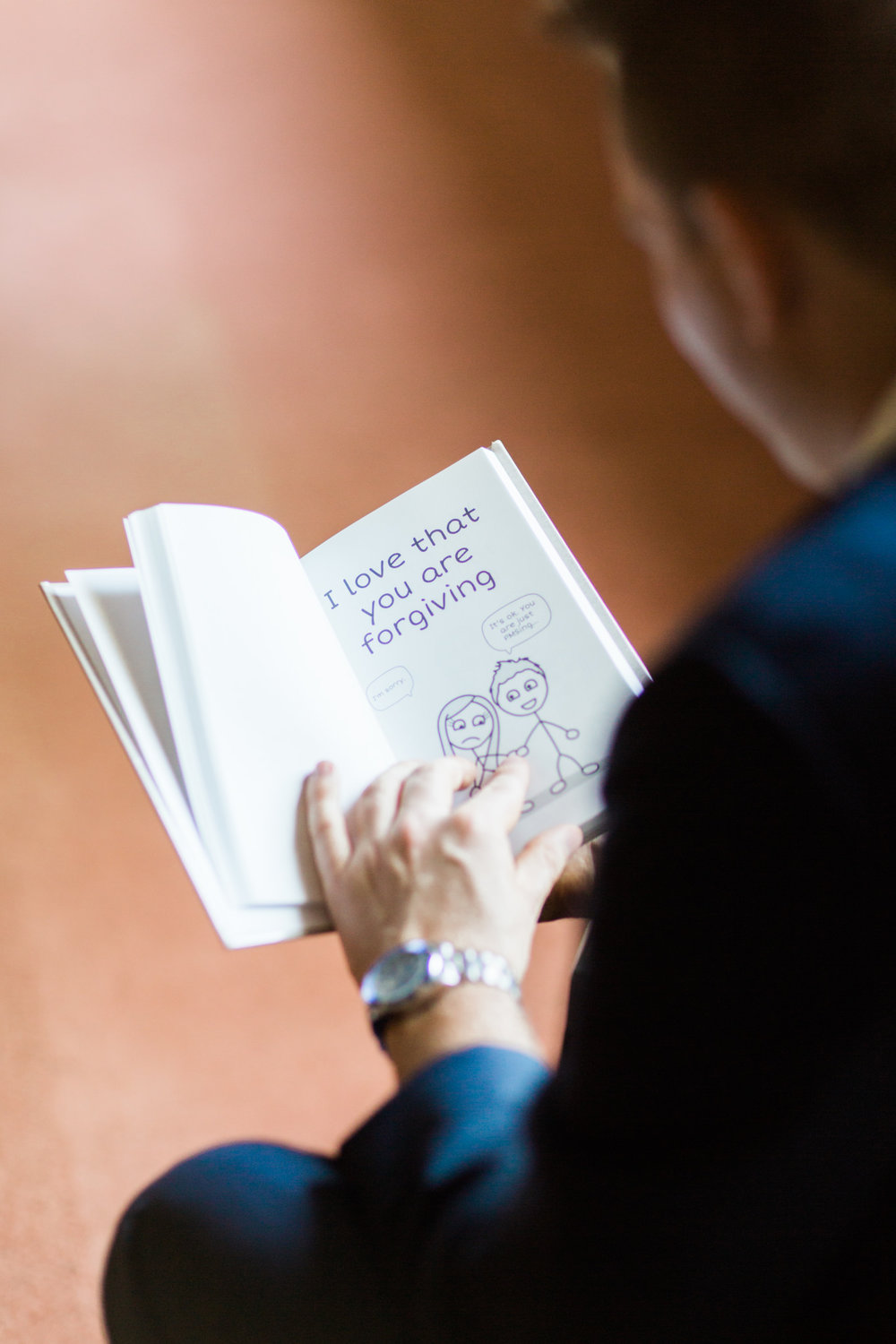 "Groom reads personalized cartoon book from the bride, words say ""I love that you are forgiving""."