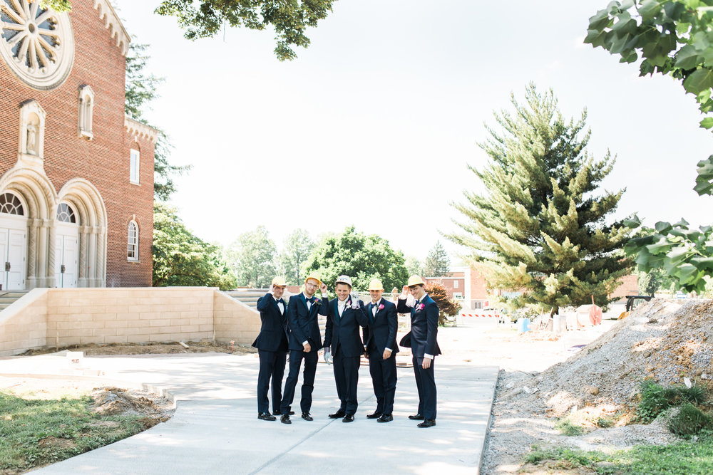 groomsman bridal party in hard hats in front of construction zone at St. Agnes Catholic Church wedding in Louisville ky