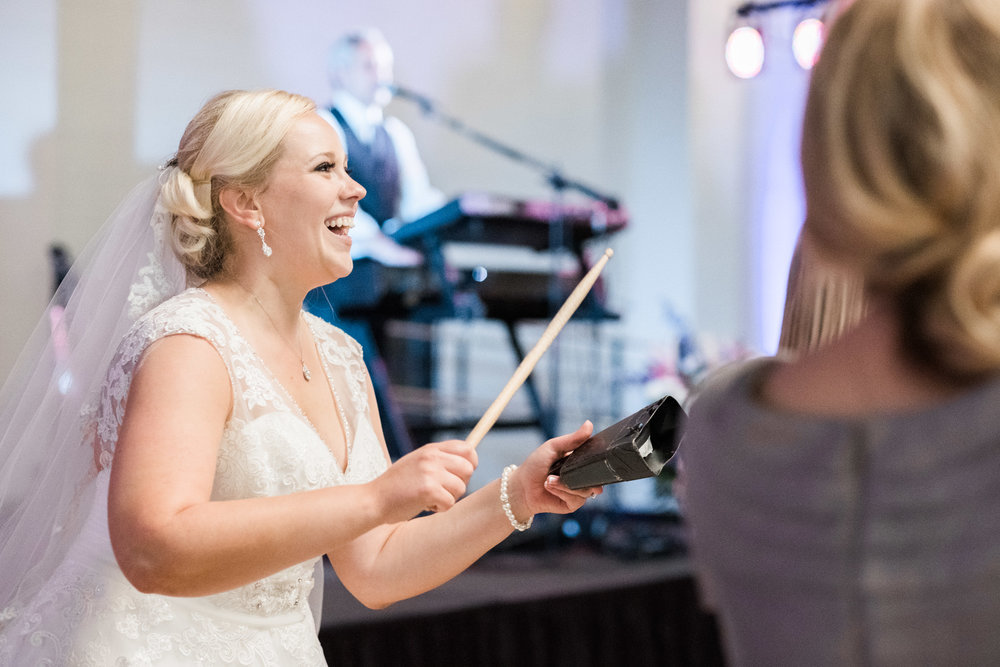 Bride hitting cowbell at wedding Bellarmine University Louisville Ky