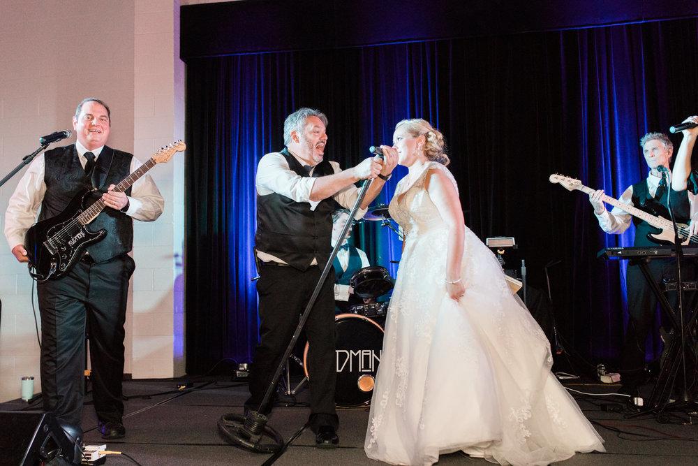 Kudmani bride singing with band on stage at bellarmine university wedding reception in louisville ky