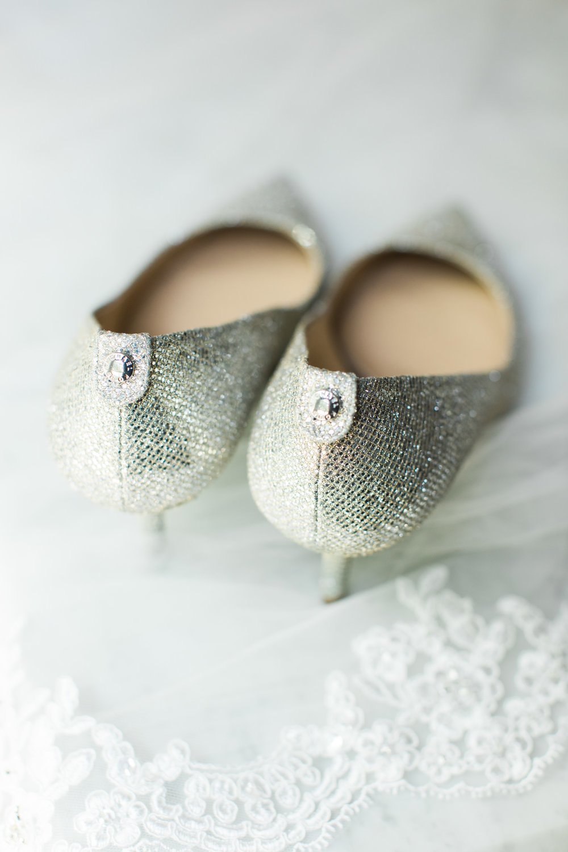 Silver glitter Michael Kors wedding shoes sitting on veil at Louisville wedding