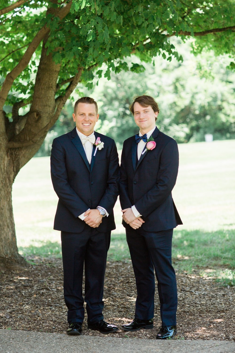 Groom and his groomsman portrait at St. Agnes Catholic Church under a tree.