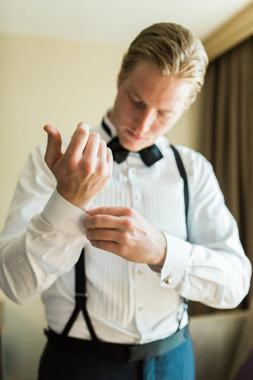 Groom with cufflink getting ready before his wedding