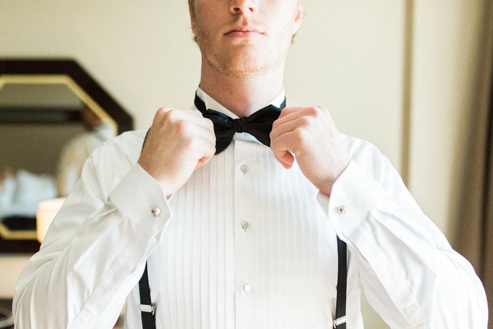 Groom adjusting his tie before his wedding