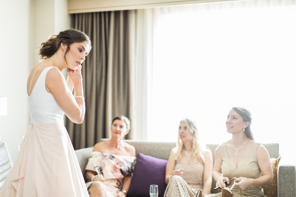 bride putting in earrings in front of her mother and bridesmaids