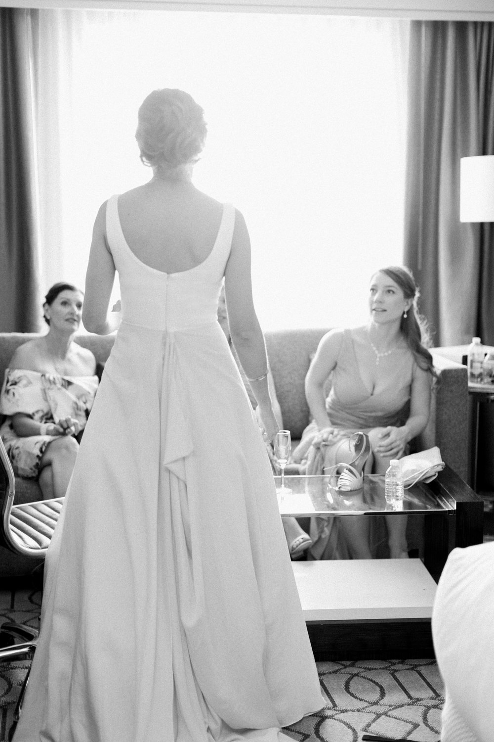 bride standing in front of bridesmaids at hotel while getting ready