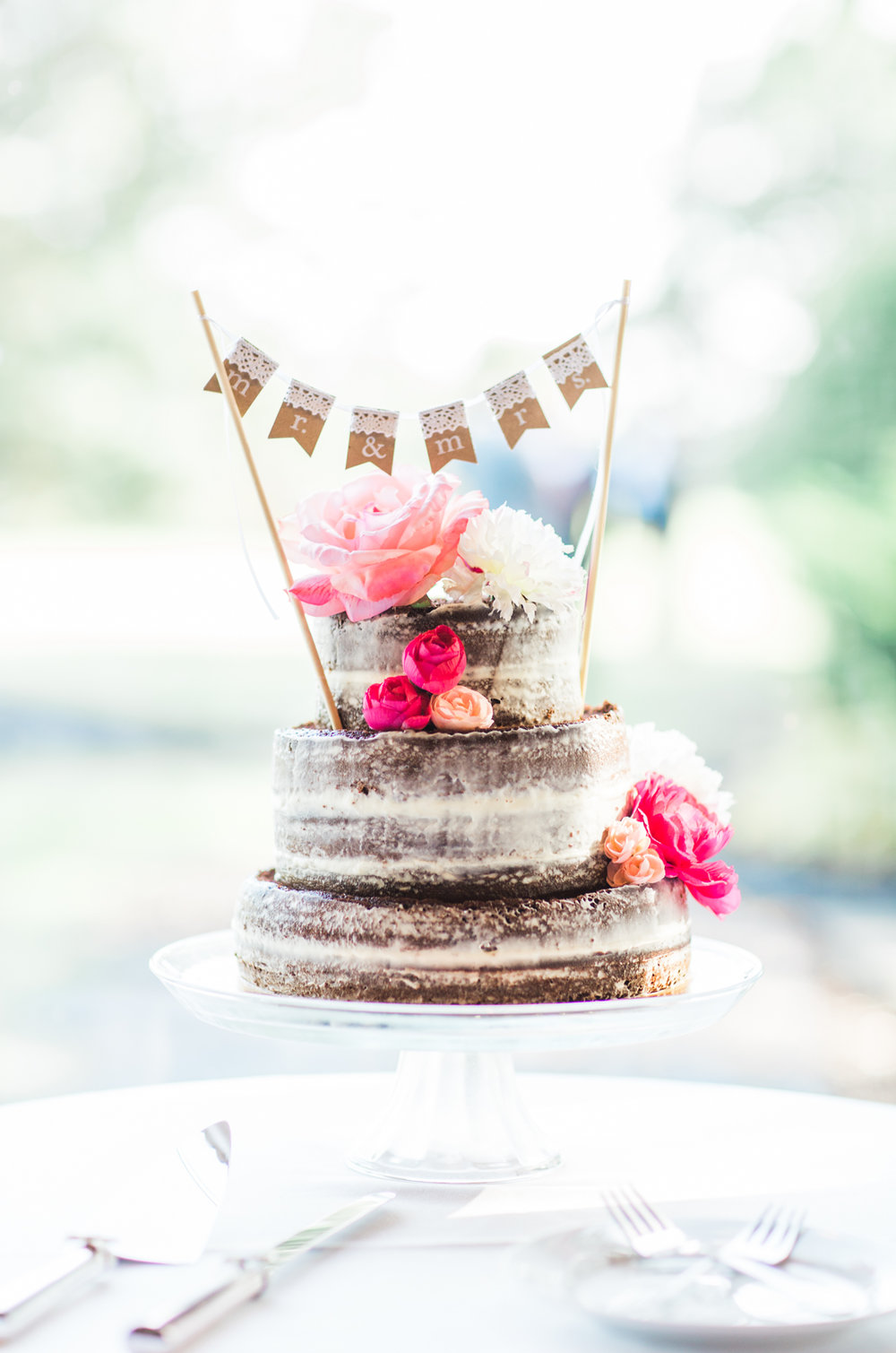 Naked chocolate wedding cake with pink flowers and burlap banner topper
