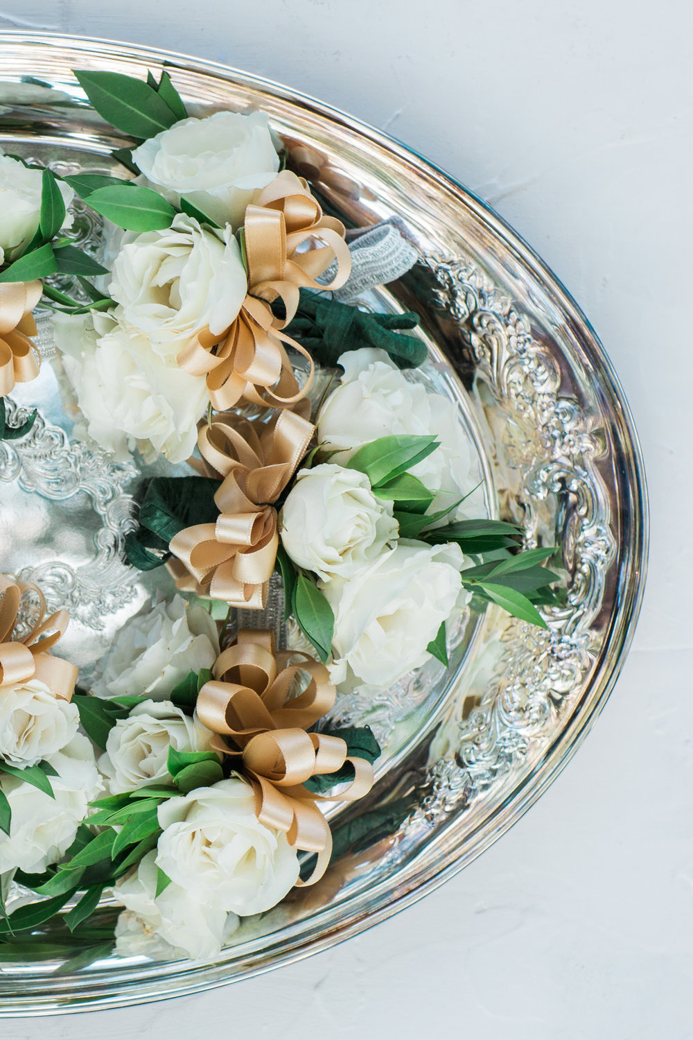 white flower boutonnieres with gold ribbons on silver platter