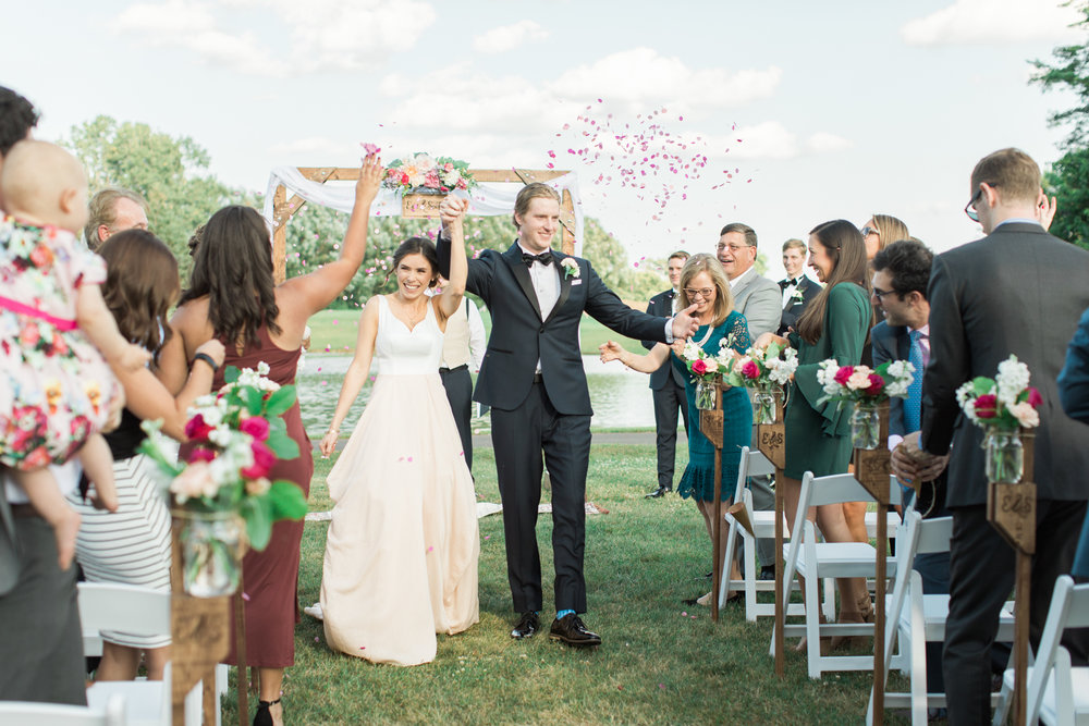 bride and groom confetti walk from the altar at little turtle club outdoor ceremony in columbus ohio