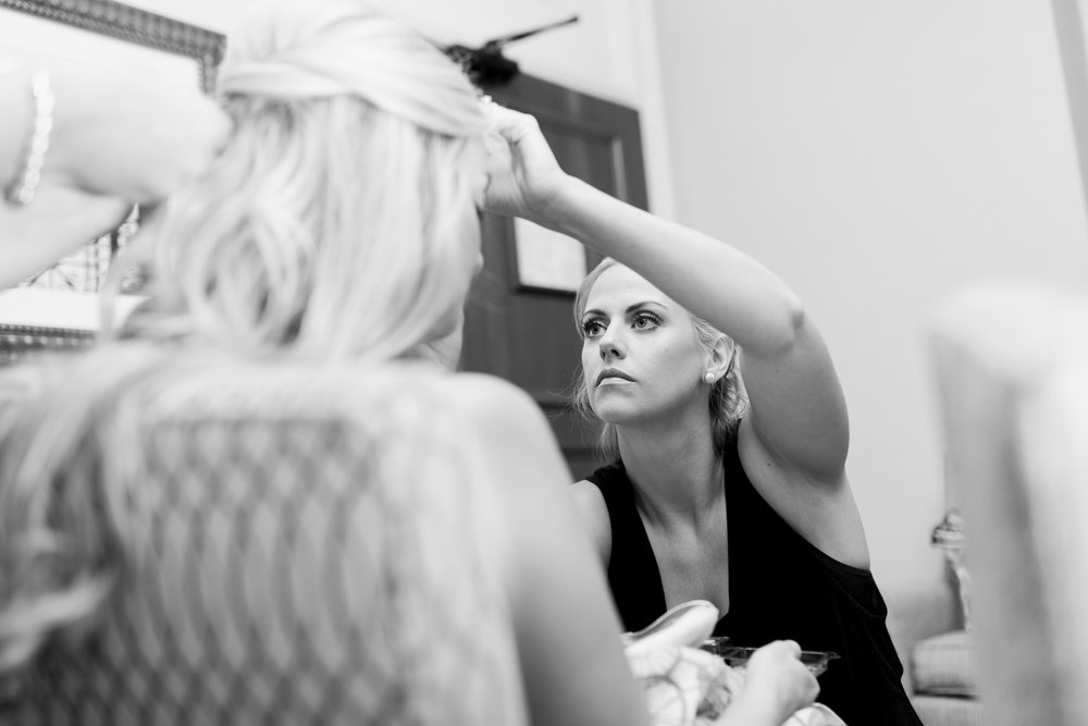 Black and white photo of bridesmaid doing bride's makeup