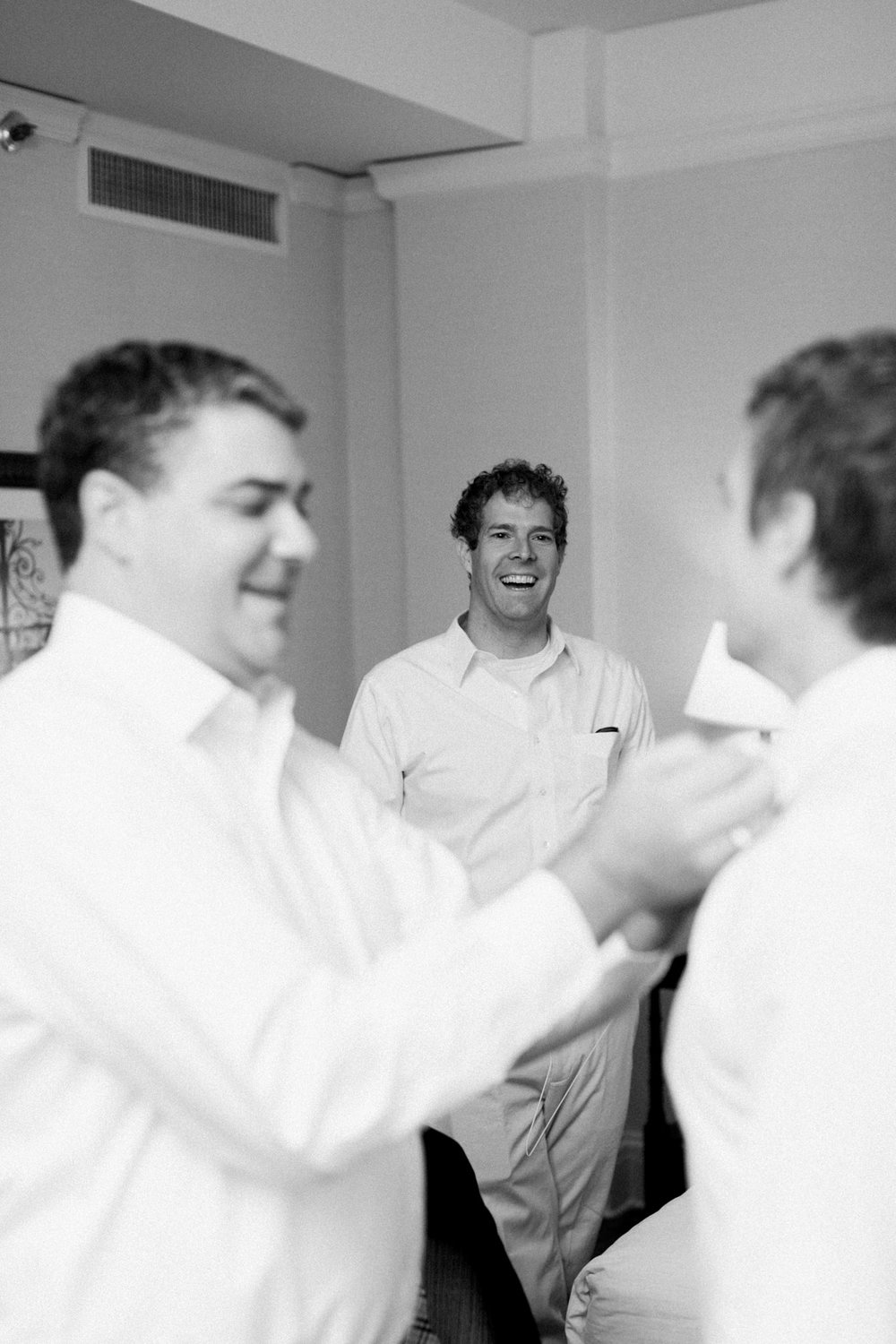 Groomsman laughing during getting ready in louisville, ky