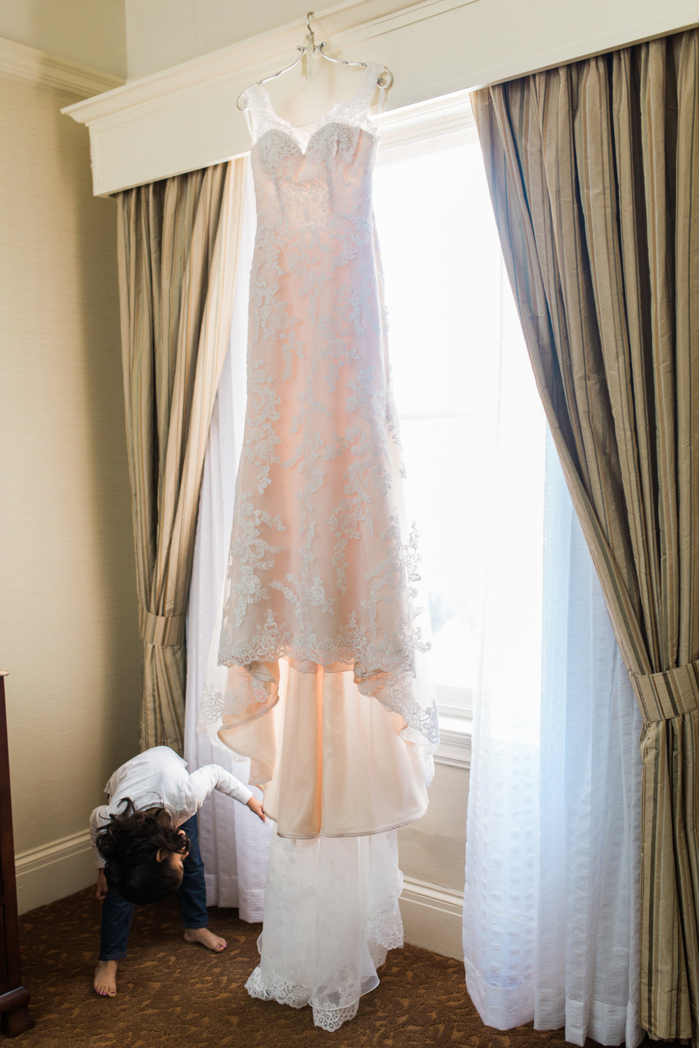Little girl peeking at wedding dress in front of hotel window