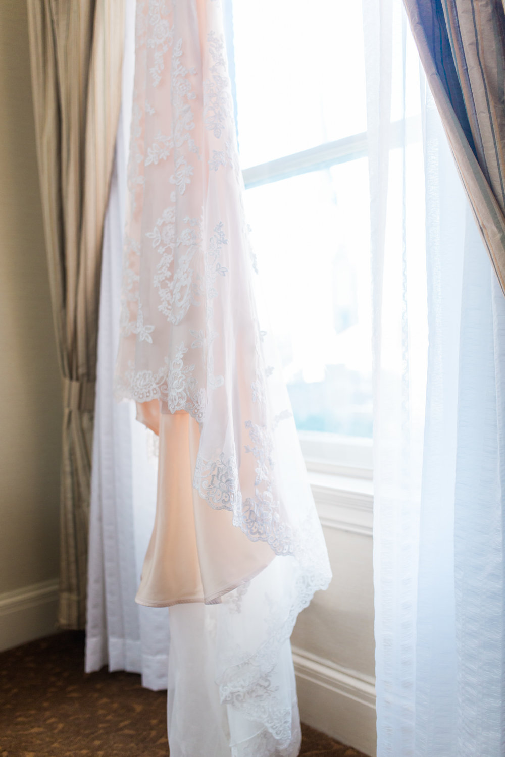 close up of white lace and peach wedding dress