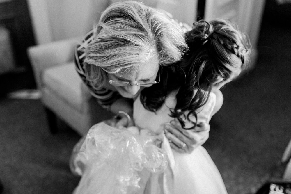 flower girl and mother of the bride hugging before the ceremony