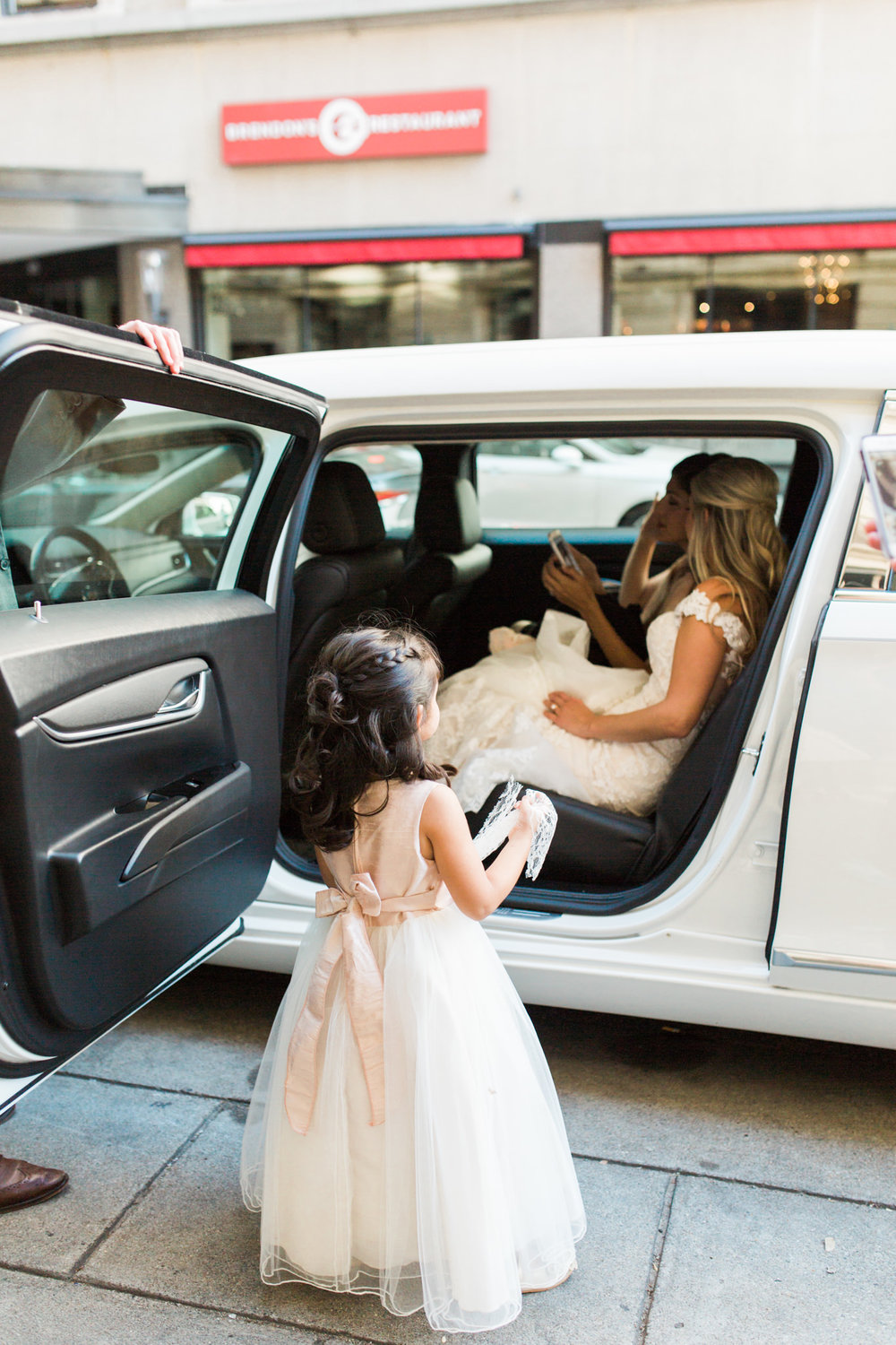 Flower girl standing in front of limo that bride is sitting in