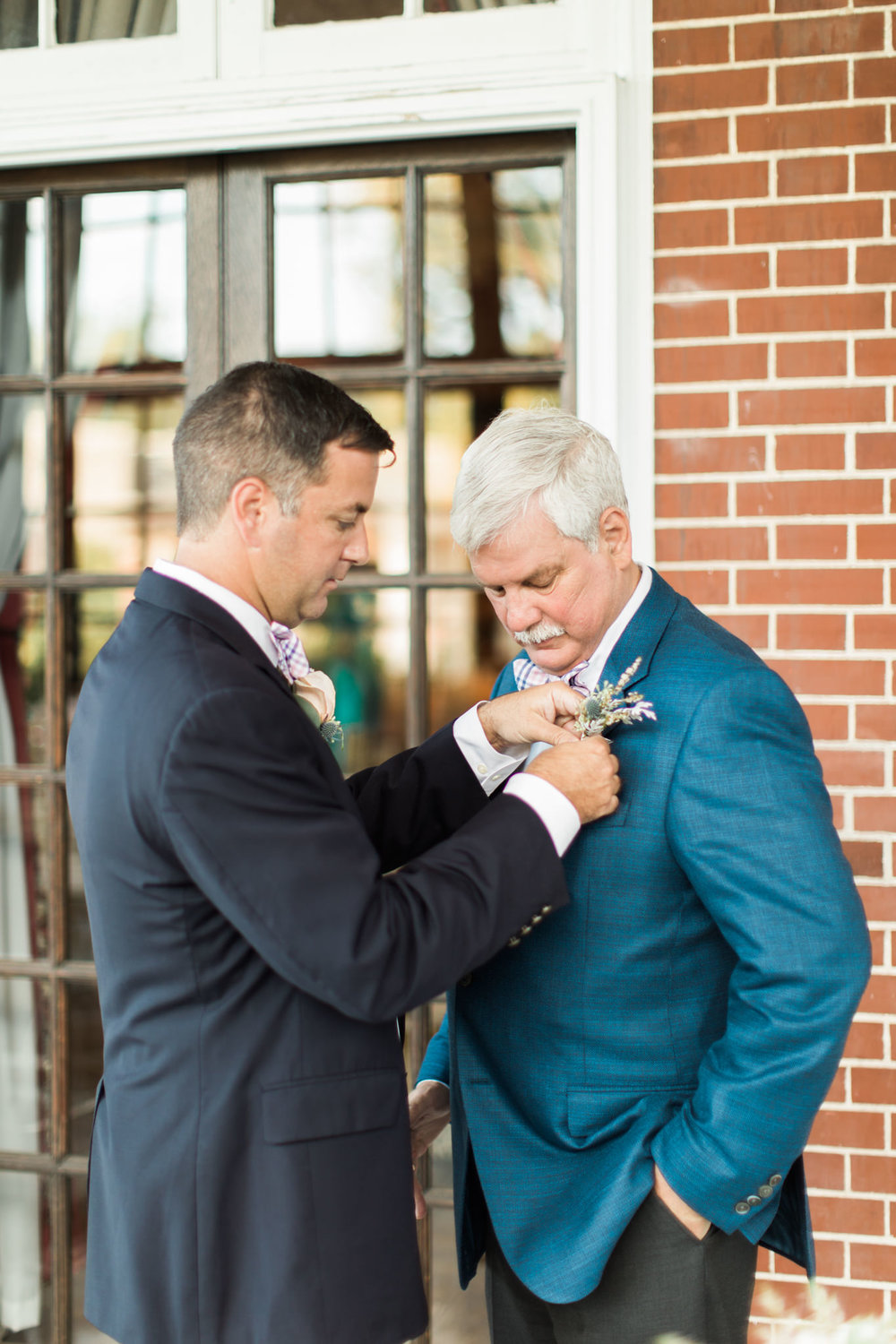 Groom pinning a boutonniere on his father