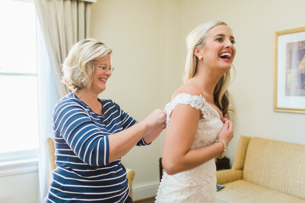 Bride laughing while mother is buttoning her dress