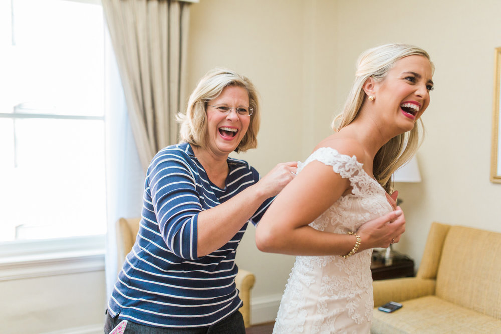 Bride and mother of the bride laughing while buttoning up the dress