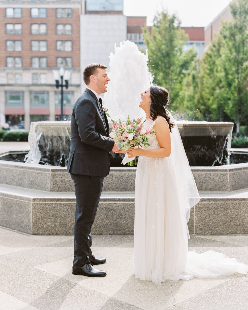 Bride with bouquet and groom laugh during first look
