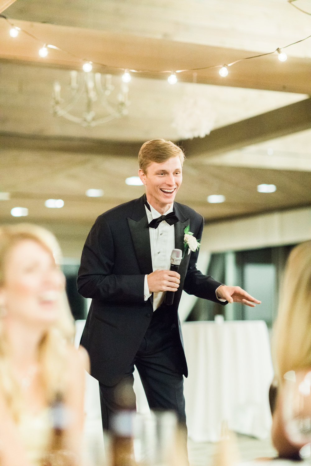 A low light wedding photography example of best man giving speech