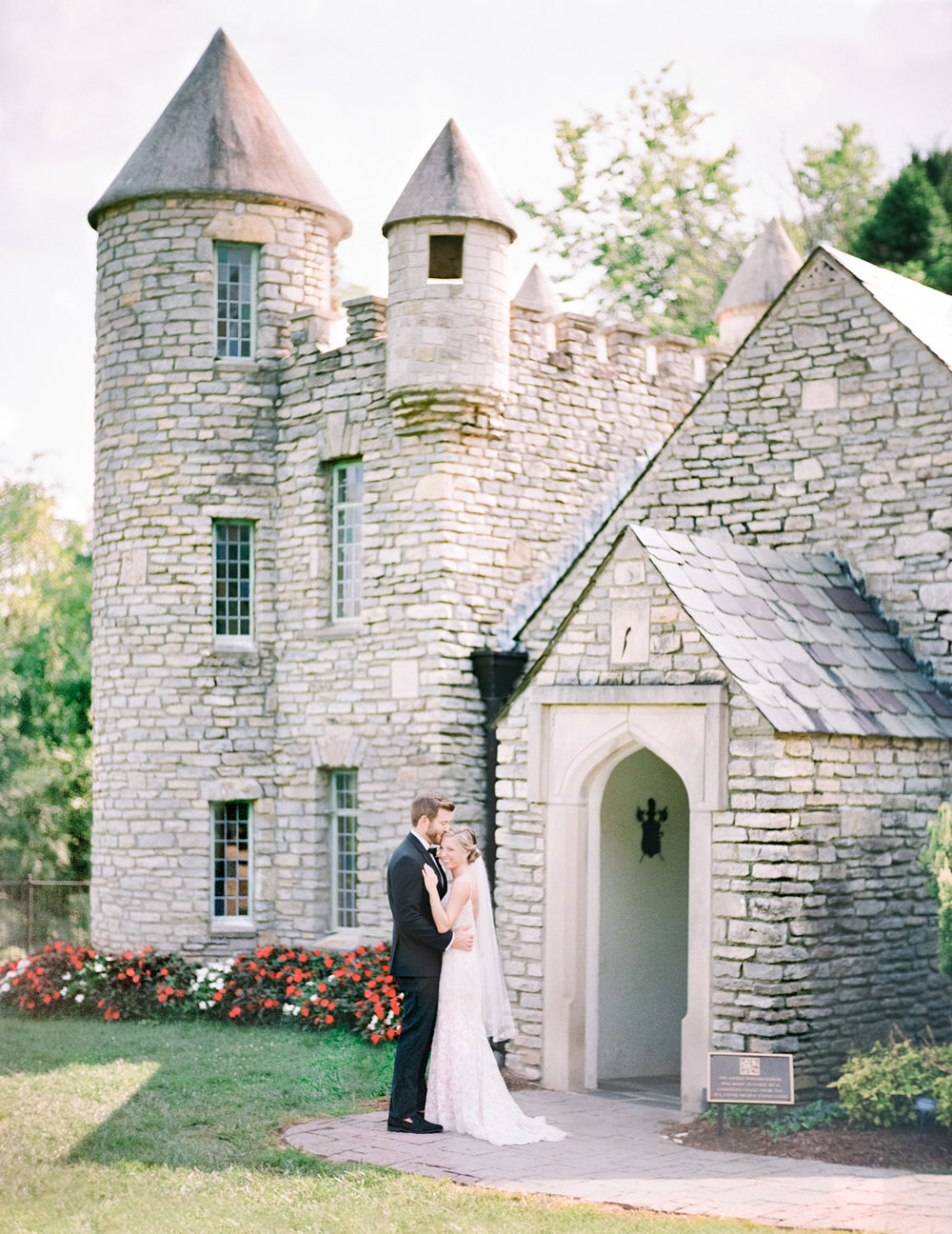 Image of bride and groom embracing in front of castle. Taken using Pentax 67 and  Schneider Cinelux Ultra MC 120mm f/2