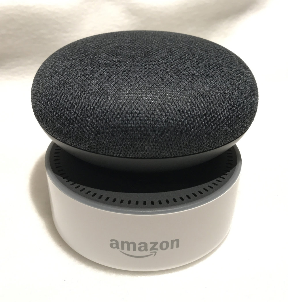 "Google Home Mini ""Charcoal"" on top of an Amazon Echo Dot ""White"""
