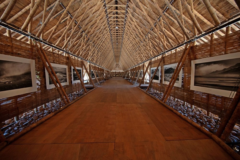 Le pavillon de bambou capté à un des rares moments où il était vide. Ce bâtiment extraordinaire, créé par l'architecte colombien Simón Vélez avec son associée Stefana Simic, est basé sur la  maloca , habitat traditionnel du bassin de l'Orénoque, et utilise les énormes bambous à croissance rapide qui poussent partout dans cette région. Le toit est en chaume de roseaux locaux.  Cette structure astucieusement ventilée restait délicieusement fraîche au milieu de la chaleur brûlante de l'été.