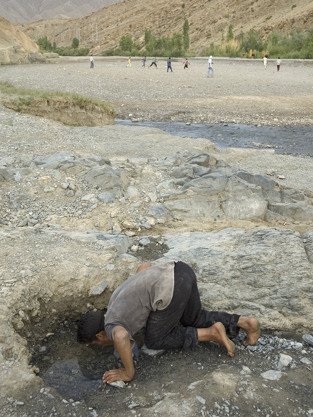 Mohammed drinking from an underground water source on the dry river.