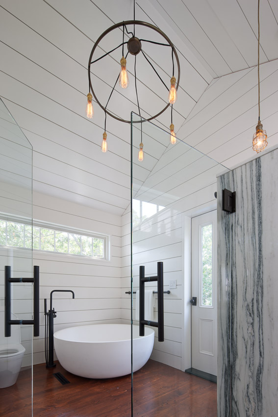 A new bathroom addition on rear of church features a marble shower and circular tub, with wide slotted pine board throughout.