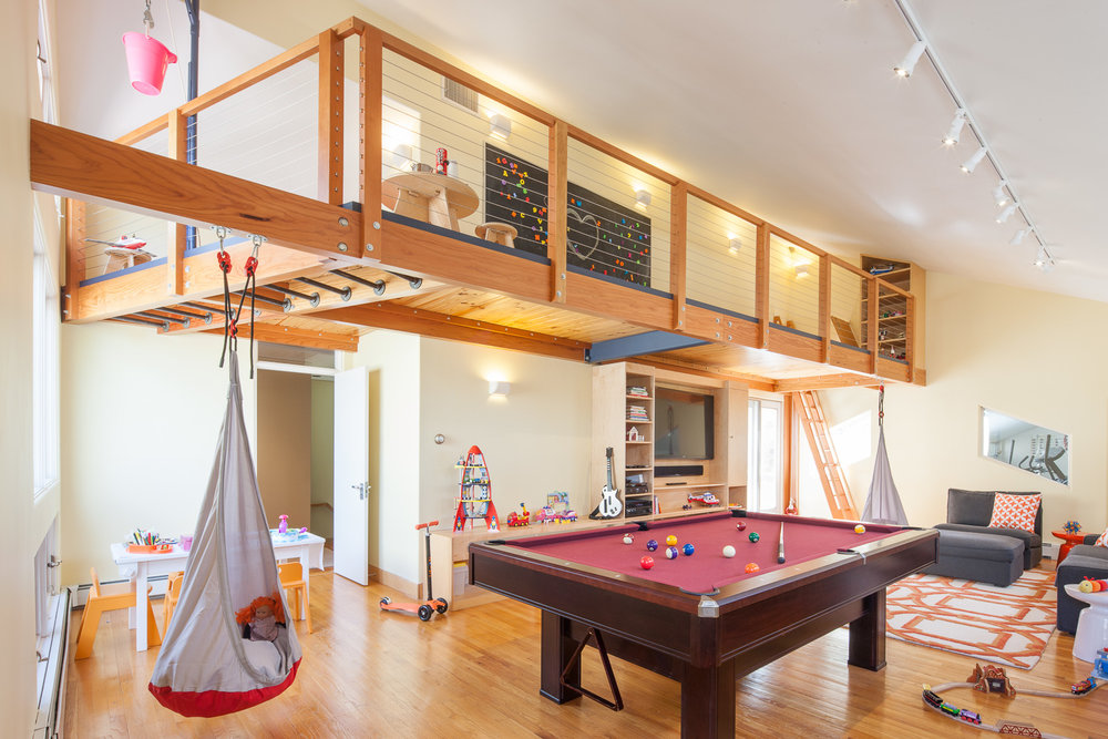 Cantilevered kids' playroom loft with trap-door ladder access, monkey bars, and well wheel.