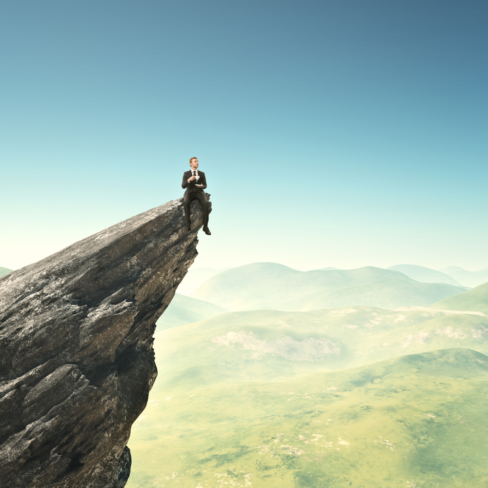 Man perched on cliff edge