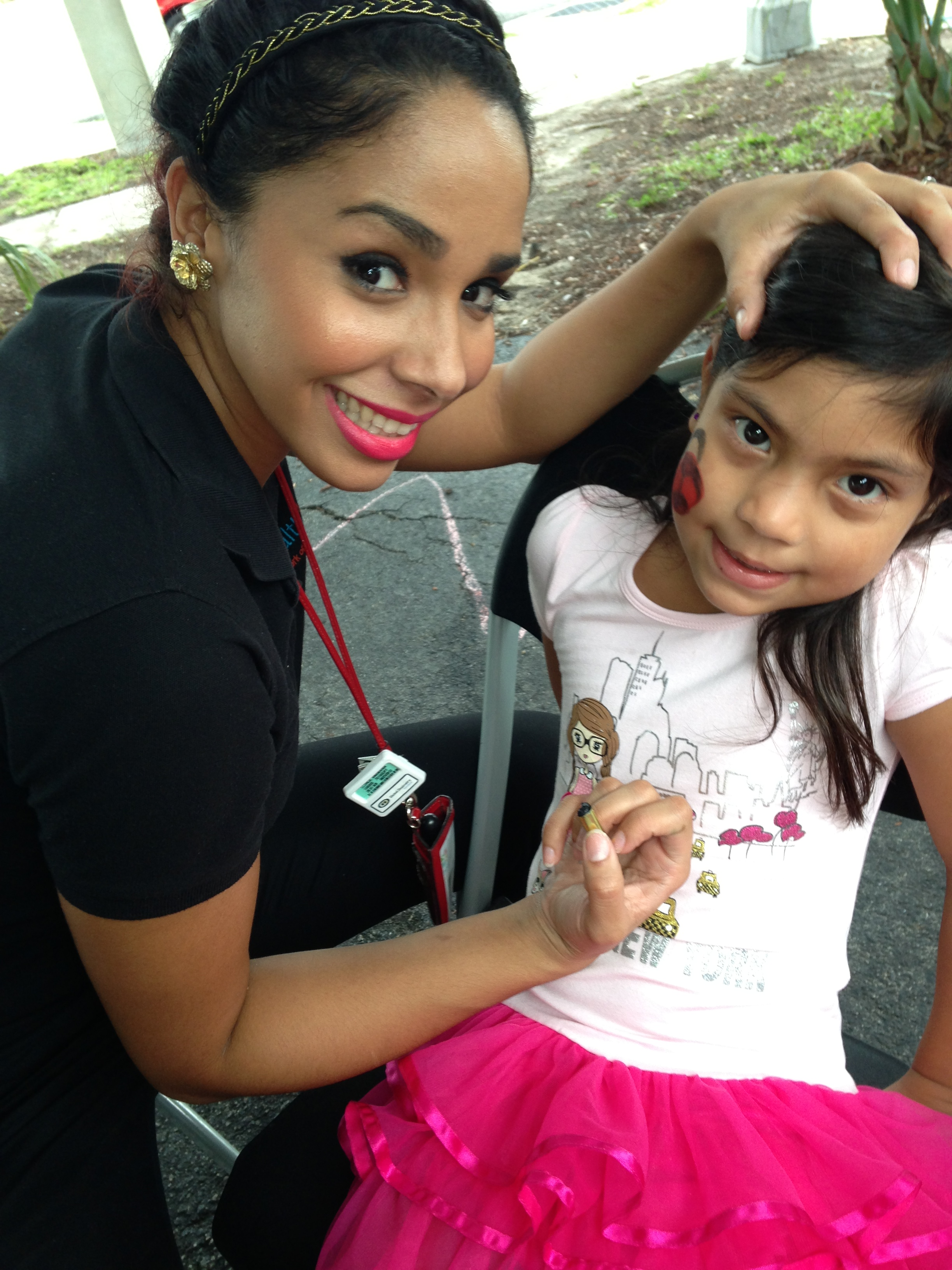 Healthcare Network of Southwest Florida dental assistant Anamaria Llorca paints a lady bug on Emily Bejarano's face during National Health Center Week festivities, Aug. 15, at the Golden Gate Community Center.