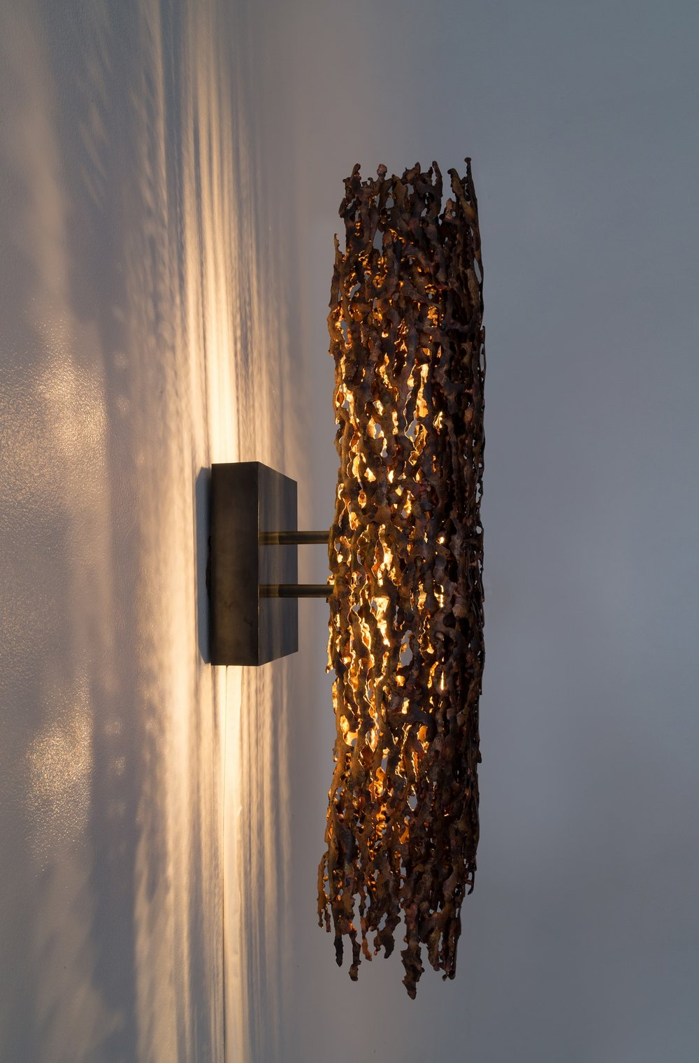 - The burnt copper form light makes a bold statement. The body of the light is hand assembled from heat-formed copper pieces into an intense compact shape. The meandering edges and varying thickness of the individual pieces contribute to a unique and engaging artistic form. The light casts dramatic shadows onto the wall creating a beautiful and varied shadows. The illumination from within the piece highlights the beautiful variation in color and texture of the copper. The raw color from the heat coloration lends a rich warmth to the piece. The copper body is supported by a minimal blackened steel armature.LED light source Narrow - 28