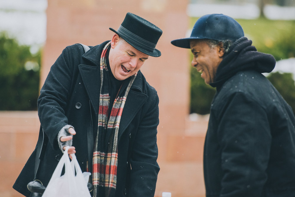 Jerry Herships, After Hours founder/director and Christmas in the Park coordinator hands off a bag of donations.