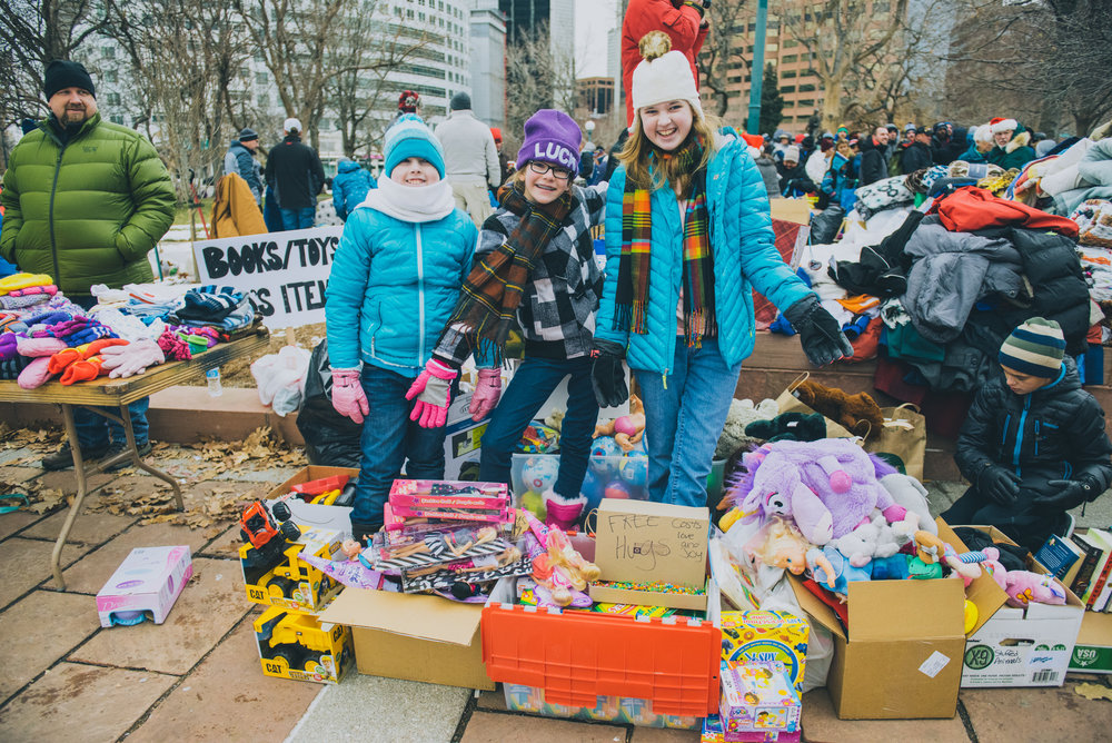 """Young volunteers giving out toys and free hugs at Christmas in the Park. They were happy to tell us, """"We're happy to be here for Christmas."""""""