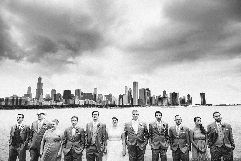 025-dramatic-bridal-party-chicago-skyline-lake-michigan-outdoors-overcast-black-white-clouds.jpg