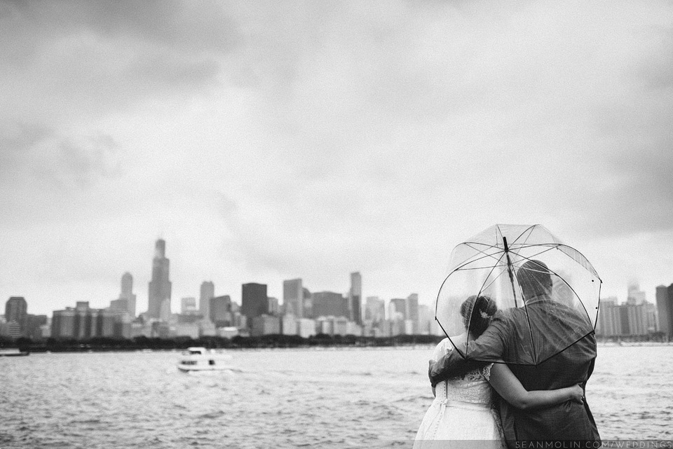 030-bride-groom-chicago-skyline-lake-michigan-overcast-outdoors-umbrella-raining-black-white.jpg