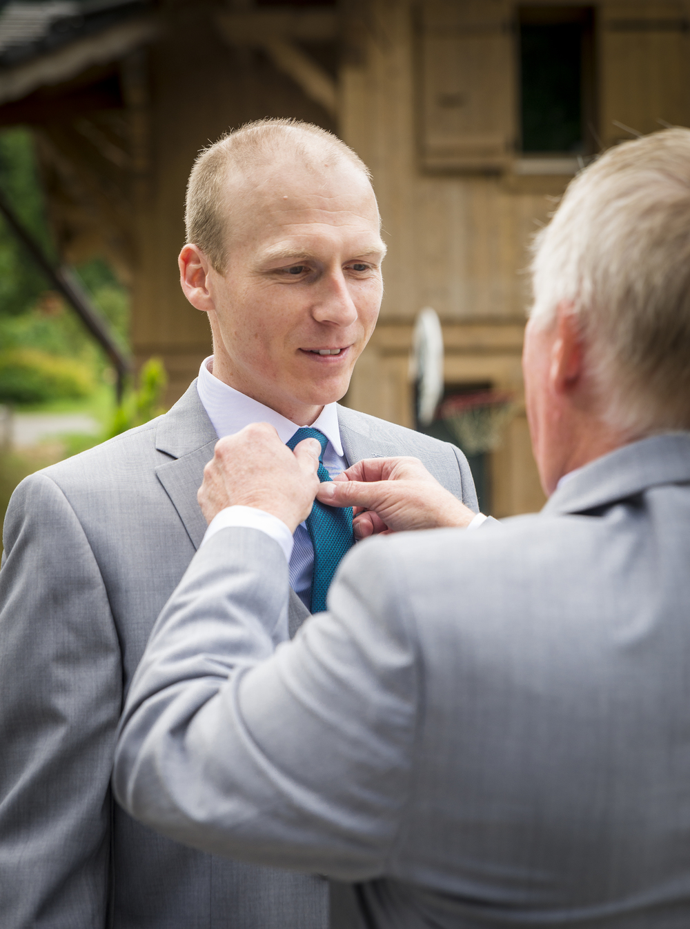 Father of the groom sorting out his sons tie.