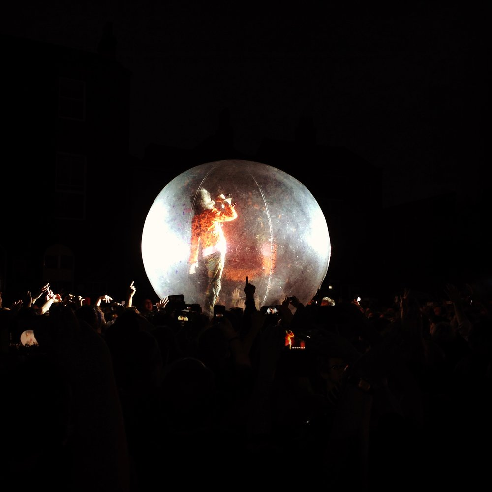 """For here I am sitting in a tin can"" - channeling Bowie in a giant ball on top of the crowd."
