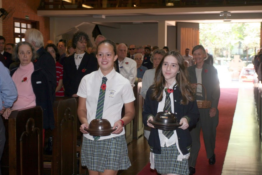 The photograph above shows Stepanie Vinaz and Beatrice McMahon from St Nicholas School leading the Poppy ladies Carol Arntsen and Judy Beer up to the altar with the poppy sales baskets and church collection