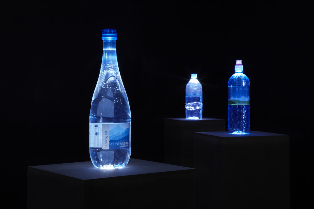 The   Source , 2013, 1L spring water bottles, LED lights, custom MDF plinths, installation view,  The Source,  Mosman Art Gallery, Sydney. Photography: Zan Wimberley. Copyright JD Reforma
