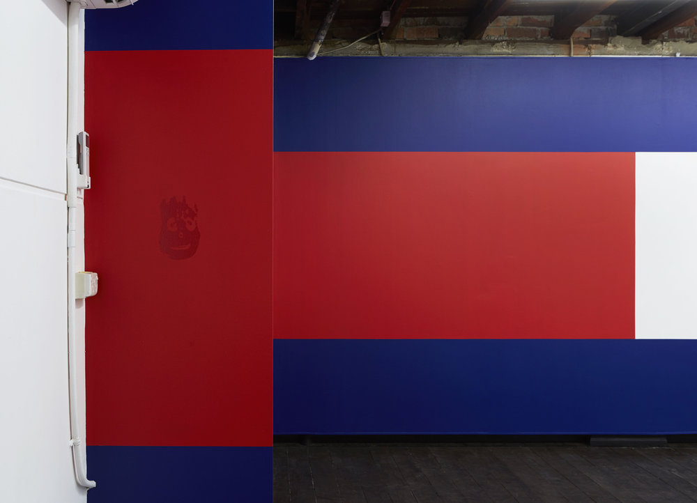 Wilson  (foreground), 2017, computer-cut adhesive vinyl scaled to the dimensions of the artist's hand, unlimited edition; and  Flag 2  (background), site-specific acrylic wall painting, installation view,  Coconut Republic , Firstdraft, Sydney. Photo: Zan Wimberley. Copyright JD Reforma