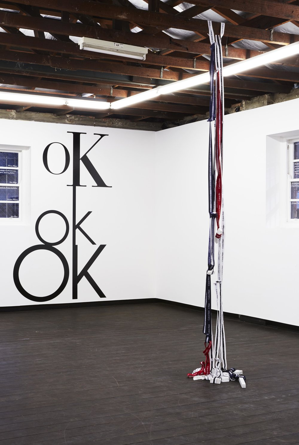 Nothing comes between  (foreground), 2017, reconfigured Calvin Klein underwear, marble; and  oK ok OK  (background), 2017, site-specific computer-cut vinyl, altered Calvin Klein logos, installation view,  Coconut Republic , Firstdraft, Sydney. Photo: Zan Wimberley. Copyright JD Reforma