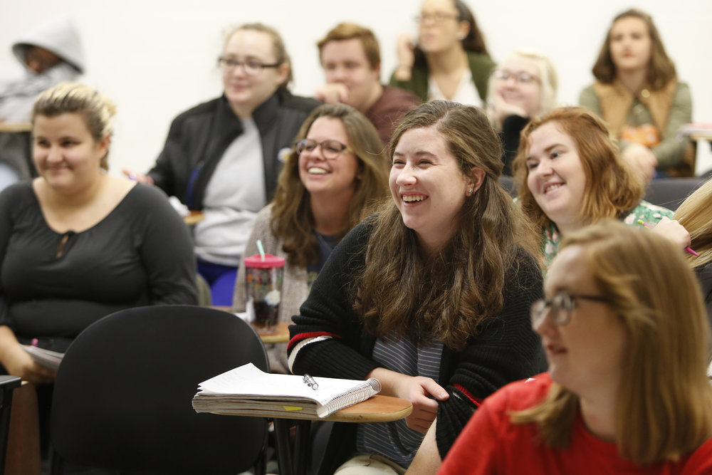 Grace and her classmates laugh at a professor's quip during government class.