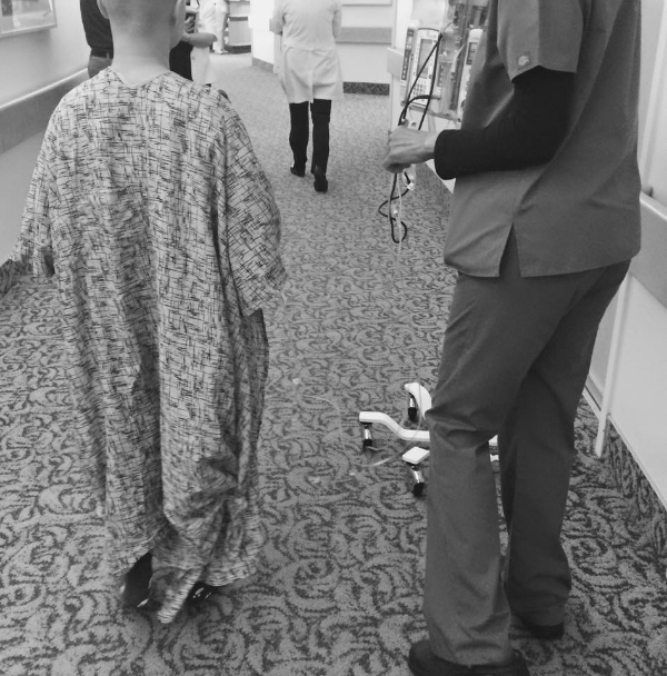 My boyfriend took this picture of my first walk on the day after my breast cancer surgery, once my nurses insisted that I get up and moving. (My gown was too long, so they had to tie the bottom to shorten it for me.)