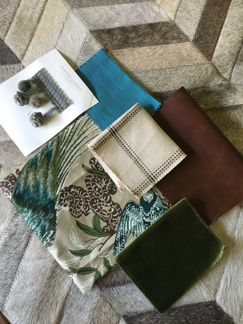 Cow hide rug, chocolate leather, lush green velvet, some flora and fauna, a pop of turquoise and of course a ball tassel fringe.