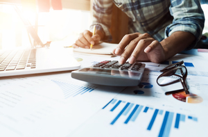 Man_working_on_financial_documents_and_calculator_300x197.jpg