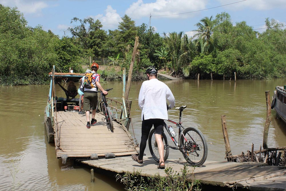 group-of-cycling-advnturers-crossing-river-on-river-boat-on-their-cycling-holiday-vietnam-to-cambodia-cycle-tour-360-expeditions - Copy.JPG